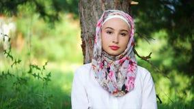 Retrato de un empollamiento y de una mujer musulmán joven, que se sienta en un bosque cerca de un árbol almacen de metraje de vídeo