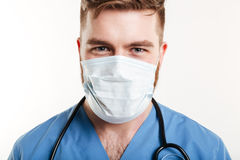 Retrato de un estetoscopio que lleva concentrado y de una máscara del cirujano de sexo masculino Fotografía de archivo libre de regalías