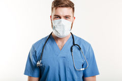 Retrato de un estetoscopio que lleva y de una máscara del cirujano de sexo masculino Fotografía de archivo