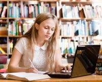Retrato de un estudiante bonito con el ordenador portátil en biblioteca Imagenes de archivo