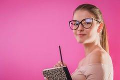 Retrato de un estudiante bonito con los vidrios que llevan de un cuaderno Foto de archivo libre de regalías