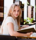 Retrato de un estudiante bonito que estudia en biblioteca con el libro abierto Foto de archivo libre de regalías