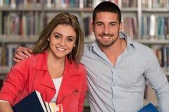 Retrato de un estudiante Couple In una biblioteca Fotografía de archivo libre de regalías