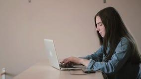 Retrato de un estudiante del adolescente de la muchacha que usa un ordenador portátil que practica surf Internet mientras que se  almacen de video