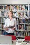 Retrato de un estudiante en una biblioteca Imagen de archivo libre de regalías