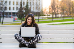 Retrato de un estudiante feliz que se sienta en el banco con el ordenador portátil al aire libre y que mira la cámara Foto de archivo