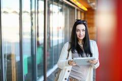 Retrato de un estudiante hermoso de la chica joven con la tableta electrónica foto de archivo