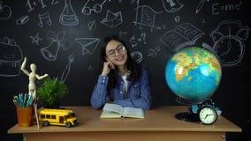 Retrato de un estudiante hermoso de la colegiala, pensando en elegir una profesión, en el fondo de un tablero negro almacen de metraje de vídeo