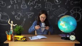Retrato de un estudiante hermoso de la colegiala, pensando en elegir una profesión, en el fondo de un tablero negro metrajes
