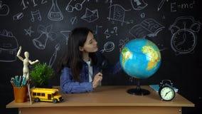 Retrato de un estudiante hermoso de la colegiala, pensando en elegir una profesión, en el fondo de un tablero negro almacen de video
