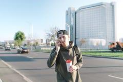 Retrato de un estudiante joven hermoso con una taza de café en las manos de un altavoz contra la perspectiva de la ciudad Y sonri Fotos de archivo