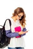 Retrato de un estudiante joven hermoso en los vidrios que mandan un SMS por smar Foto de archivo libre de regalías