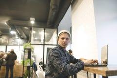 Retrato de un estudiante joven que se sienta en un café en la tabla y que usa un ordenador El inconformista funciona con un orden Imagen de archivo libre de regalías