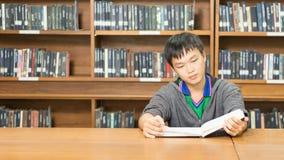Retrato de un estudiante joven serio que lee un libro en una biblioteca Imagen de archivo