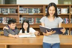 Retrato de un estudiante joven serio que lee un libro en una biblioteca Fotos de archivo