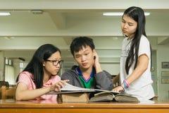 Retrato de un estudiante joven serio que lee un libro en una biblioteca Foto de archivo libre de regalías