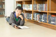 Retrato de un estudiante joven serio que lee un libro en una biblioteca Foto de archivo