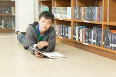 Retrato de un estudiante joven serio que lee un libro en una biblioteca Imagen de archivo libre de regalías