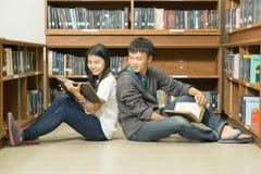 Retrato de un estudiante joven serio que lee un libro en una biblioteca Imagenes de archivo