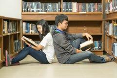 Retrato de un estudiante joven serio que lee un libro en una biblioteca Fotos de archivo libres de regalías