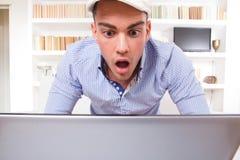Retrato de un estudiante masculino chocado que mira el monitor de su revestimiento Imágenes de archivo libres de regalías