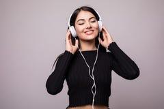 Retrato de un estudiante de mujer hermoso que escucha la música en el fondo blanco Fotografía de archivo libre de regalías