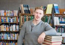 Retrato de un estudiante que mira la cámara en biblioteca de universidad Imagenes de archivo