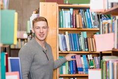 Retrato de un estudiante que mira la cámara en biblioteca de universidad Imagen de archivo libre de regalías