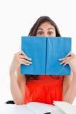 Retrato de un estudiante que oculta detrás de un libro azul Imagen de archivo libre de regalías