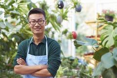 Retrato de un florista de sexo masculino joven feliz en tienda Fotografía de archivo