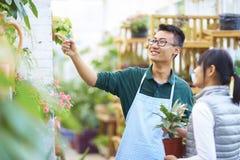 Retrato de un florista de sexo masculino joven feliz en tienda Fotografía de archivo libre de regalías