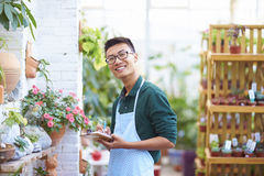 Retrato de un florista de sexo masculino joven feliz en tienda Imagen de archivo
