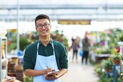 Retrato de un florista de sexo masculino joven feliz en tienda Imágenes de archivo libres de regalías