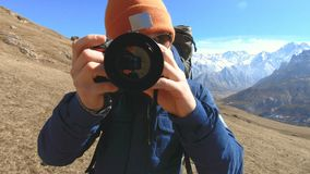 Retrato de un fotógrafo barbudo feliz del viajero en gafas de sol y un sombrero con una cámara refleja en sus manos y tomar almacen de video