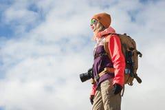 Retrato de un fotógrafo turístico de la muchacha del inconformista con una cámara en gafas de sol y un sombrero contra la perspec fotografía de archivo