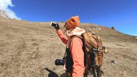 Retrato de un fot?grafo feliz del viajero de la muchacha en un sombrero y gafas de sol con una c?mara alrededor de su cuello y de almacen de metraje de vídeo