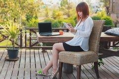Retrato de un freelancer de sexo femenino sonriente de los jóvenes que usa las tabletas Imágenes de archivo libres de regalías