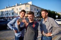 Retrato de un grupo de amigos sonrientes, preparándose para hacer el selfie en cámara en fondo urbano Fotografía de archivo