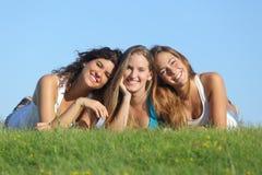 Retrato de un grupo de mentira sonriente de tres muchachas felices del adolescente en la hierba Imágenes de archivo libres de regalías