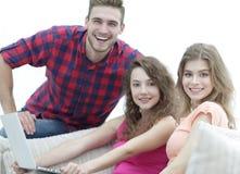 Retrato de un grupo de gente joven que se sienta en el sofá en la sala de estar Imagen de archivo libre de regalías