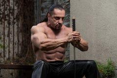 Retrato de un guerrero antiguo muscular con la espada Imágenes de archivo libres de regalías