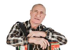 Retrato de un hombre, abuelo que juega el acordeón O aislado foto de archivo