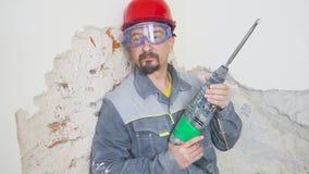 Retrato de un hombre adulto en un casco en su cabeza y con un perforador en su mano almacen de video