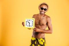 Retrato de un hombre africano en el traje de baño que sostiene el reloj de pared Imagenes de archivo