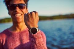 Retrato de un hombre africano joven que muestra al suyo el reloj Foto de archivo libre de regalías