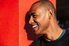 Retrato de un hombre africano de risa feliz que parece ausente al aire libre Fotos de archivo libres de regalías
