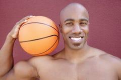 Retrato de un hombre afroamericano joven con baloncesto en hombro sobre fondo coloreado Fotografía de archivo