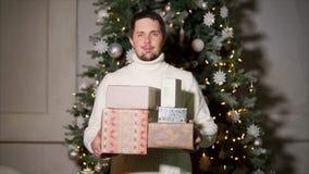 Retrato de un hombre alegre en un suéter que guarda las cajas con los regalos en fondo de un árbol de navidad almacen de metraje de vídeo