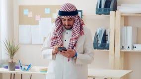 Retrato de un hombre alegre en una oficina del aspecto de Oriente Medio que sostiene un teléfono en su mano Al su llevar principa metrajes