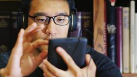 Retrato de un hombre asiático en vidrios Utiliza una tableta en la biblioteca Él se sienta en el fondo de estantes metrajes